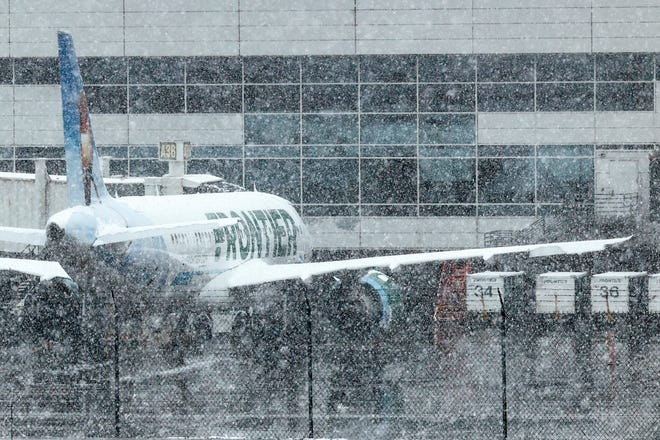 A Frontier Airlines plane sits at a gate at Denver International Airport on March 13, 2021, in Denver.
