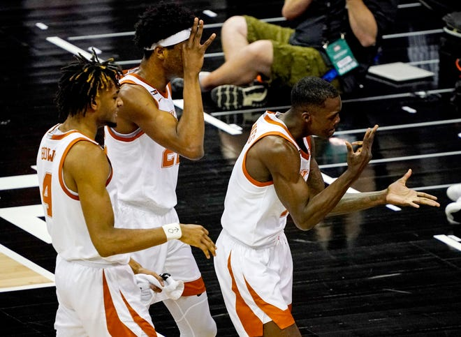 Texas Longhorns guard Andrew Jones (1) celebrates with forward Kai Jones (22) and forward Greg Brown (4) after scoring against the Oklahoma State Cowboys during the first half at T-Mobile Center.