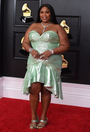 Lizzo arrives at the Grammys in a seafoam green, knee-length dress with ruching.