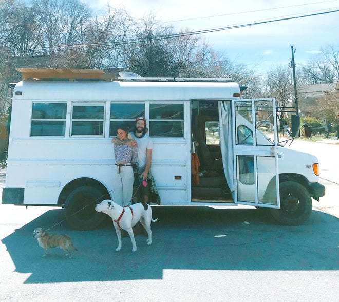 Musician couple Sam and Erin Burchfield (aka Pip the Pansy) stand beside the bus they now call home. (Photo courtesy of the Burchfields)