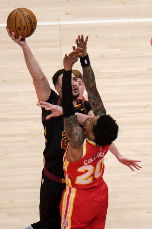Cavaliers forward Larry Nance Jr. (22) shoots over Atlanta Hawks forward John Collins (20) during the Cavs' 100-82 loss Sunday night in Atlanta. [Ben Gray/Associated Press]