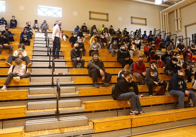 Eighth grade boys sit socially distanced in the gymnasium Monday during the first day back for in-person classes at Hyre Middle School in Akron.