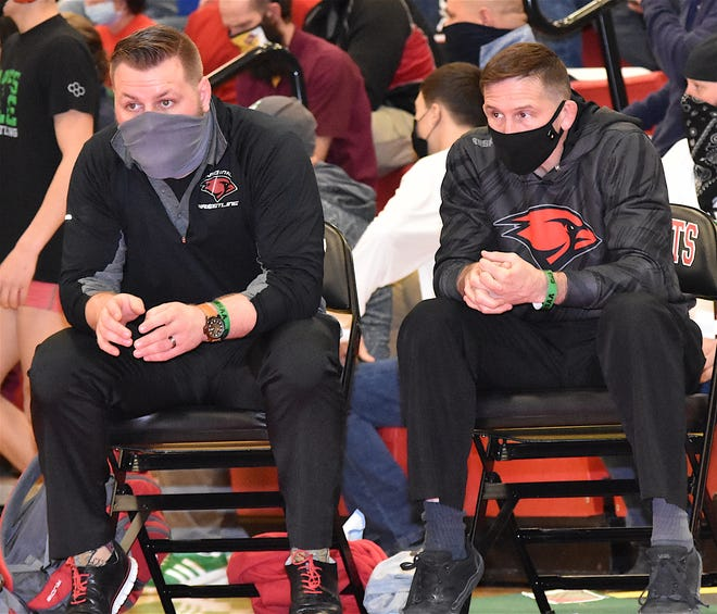 Sandy Valley head coach Greg Donahue (right) and assistant Billy Natale watch a first-round match at the 2021 OHSAA Wrestling Championships. The Cardinals had seven state qualifiers this season.
