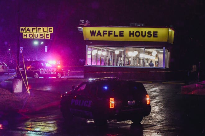 Police vehicles flash their lights in the parking lot of Waffle House on Vandiver Drive on Sunday evening in Columbia.