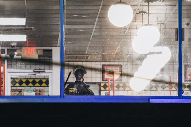 A police officer stands inside of a Waffle House after shots were fired at the restaurant late on Sunday evening in Columbia.