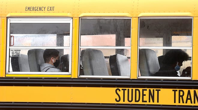 Hickman High School students wear masks while riding home from school on March 15.