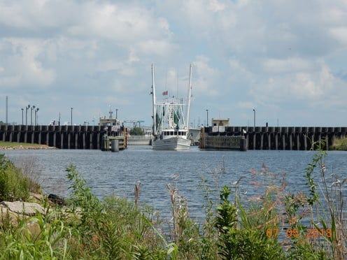 A shrimp boat passes through the Leon Theriot Lock along Bayou Lafourche in Golden Meadow.