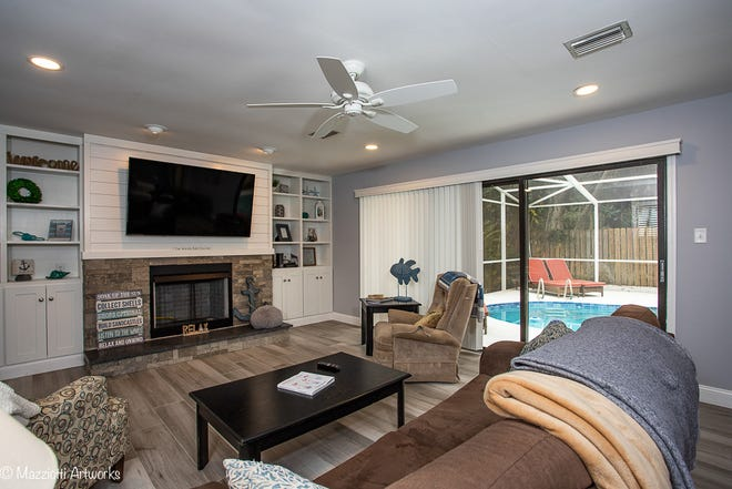 The large family room, with a built-in entertainment center and sliders to the pool, offers plenty of space to relax, get cozy by the fireplace or host a game night with friends in the bar area.