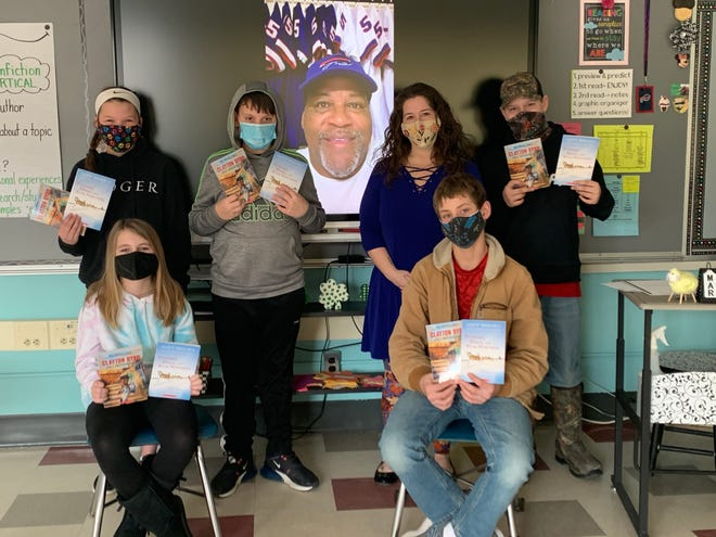 Wayland-Cohocton students show off the books they received from former Buffalo Bills linebacker Mark Maddox, pictured on the screen delivering a video message to the class.