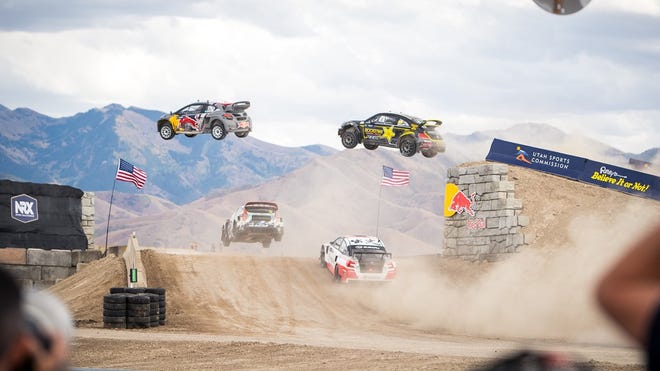 Nitro Rallycross, with race cars leaping over jumps as other tackle a hill below.