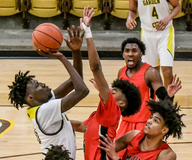 Garden City Community College's Mohamed Diarra, left, goes up for a basket in the lane over Northwest Technical's Hants Louis-Jeune Saturday at Perryman Athletic Complex.  GCCC came back from 20 points down in the second half to claim the victory, 78-77.