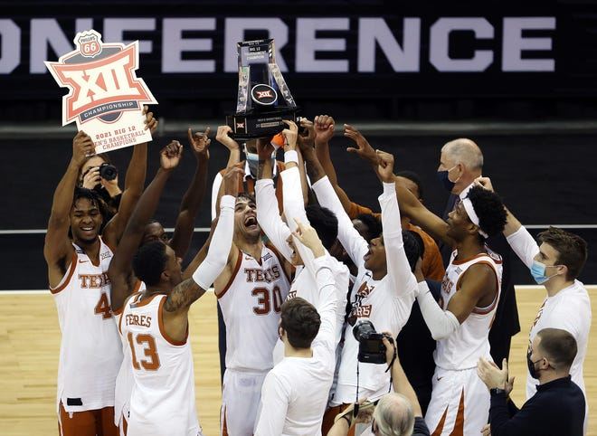 The Texas Longhorns celebrate after a 91-86 triumph against Oklahoma State in the Big 12 Tournament championship game at the T-Mobile Center in Kansas City, Missouri, on March 13, 2021.