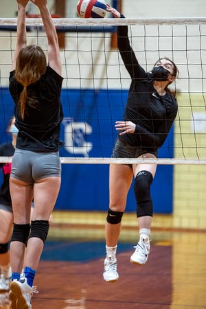 Galesburg High School senior Lauren Livingston spikes the ball over a Silver Streaks teammate during volleyball practice on Monday, March 8 at Churchill Junior High School.