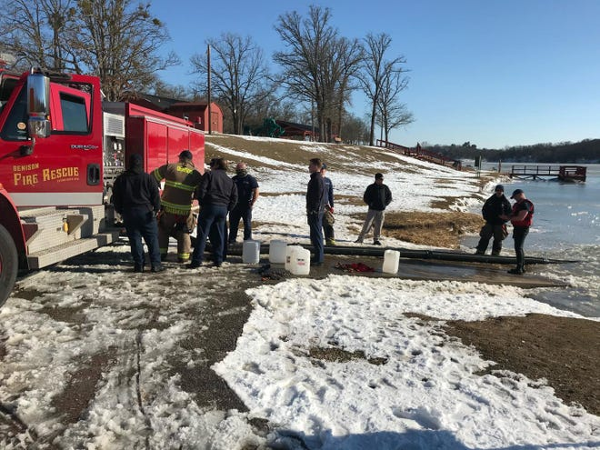 Members of Denison Fire Rescue manually fill a truck with water during winter storms last month. The city is looking for ways to prevent future damage similar to that seen during storms last month.