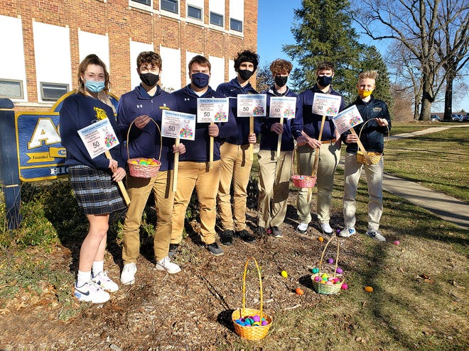 Ava Hiveley, from left, Domminick Alber, Cade Geiken, Connor Senneff, Ollie Arndt, Drew Ege and Lane Pierson hold up signs and Easter eggs Thursday to show off a fundraiser the junior class is holding for post-prom at Aquin Catholic High School in Freeport.