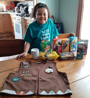Kaylee Euler shows off a few of the 693 boxes of Girl Scout cookies she sold this year as part of the annual fundraising campaign. She prefers the Lemon-Ups cookies with a big glass of milk.