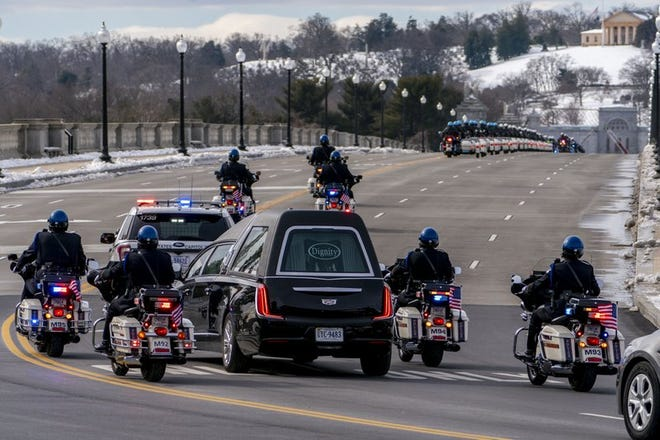 In this Feb. 3, 2021 file photo, a hearse carrying the remains of U.S. Capitol Police officer Brian Sicknick makes its way to Arlington National Cemetery after Sicknick was lying in honor at the U.S Capitol, Wednesday, Feb. 3, 2021, in Washington.