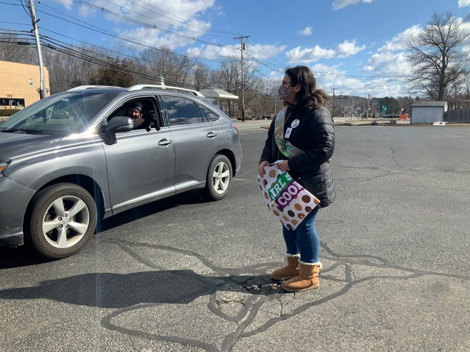 Carmela Silvia helps a customer buy Girl Scout cookies at 475 Boston Post Road (Rte. 20) in Sudbury, March 14, 2021.