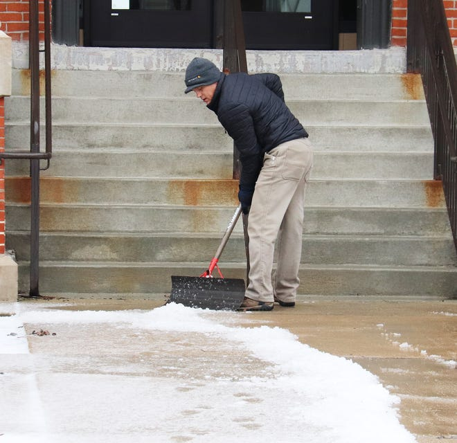 Ray Gerth, maintenance worker at the Historic Livingston County Courthouse, scoops ice from the sidewalk in front of the north steps  Monday afternoon.