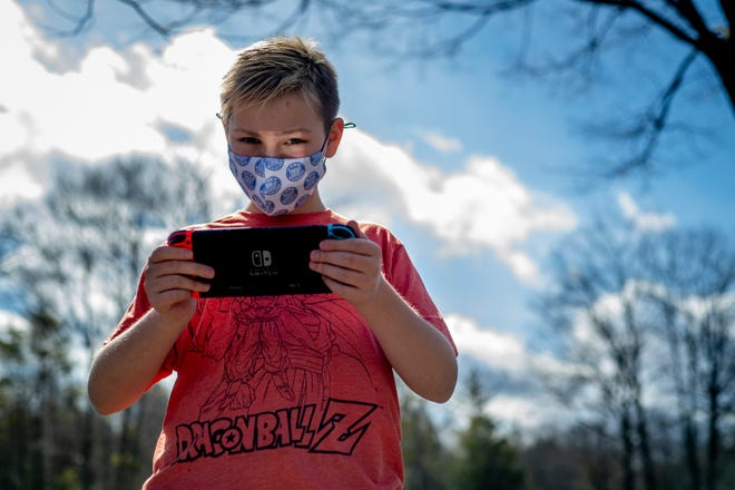 Twelve-year-old Wyatt Hale of York poses outside his home on March 14, 2021, with a Nintendo switch, one of the devices he uses to participate in the York Parks and Recreation esports league.