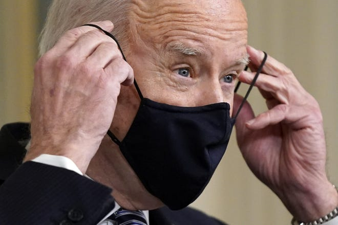 President Joe Biden puts on his face mask after speaking about the COVID-19 relief package in the State Dining Room of the White House, March 15.