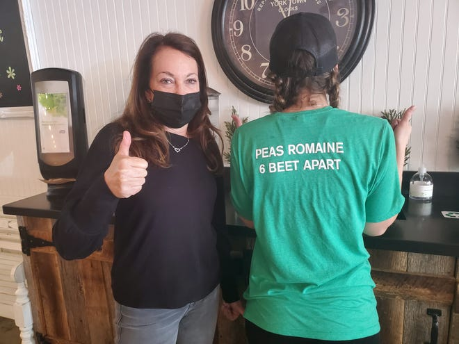 Debra Lakow, owner of Field of Greens restaurants in  West Palm Beach, Palm Beach and Wellington, poses with an employee at the West Palm Beach location. Lakow said she wants to see businesses fully open, but also wants the governor to issue mask mandates. March 15, 2021.