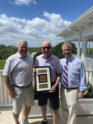 Joe Steranka (left), a member of the Honda Classic board of directors, and Honda Classic executive director Ken Kennerly (right), presented Tim Rosaforte with a plaque honoring him as the winner of the Distinguished Writers award that will be named for him.