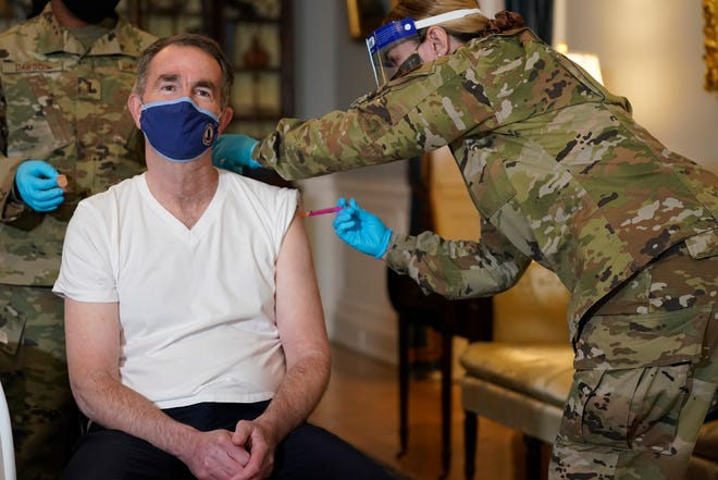 Virginia Gov. Ralph Northam receives a COVID-19 vaccination from Lt. Col. Kris Clark, of the Virginia Air National Guard at the Governors Mansion in Richmond, Va., Monday, March 15, 2021.  Northam got a shot of the Johnson & Johnson coronavirus vaccine, joining the growing number of Virginians who are being inoculated against the potentially deadly disease.  (AP Photo/Steve Helber)
