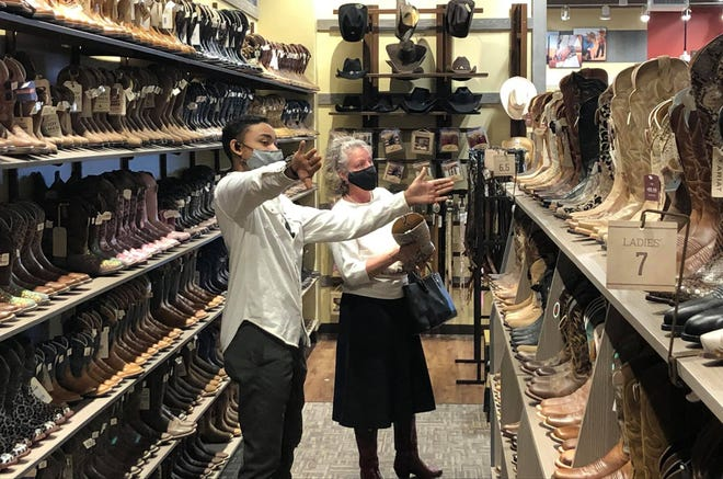 Boot Barn floor manager David Zuniga assists a customer in Colonial Heights on March 11, 2021.