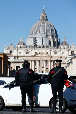 Carabinieri police officers stop a car at a road block near St' Peter's Basilica, in background, in Rome, Monday, March 15, 2021. Half of Italy's regions have gone into the strictest form of lockdown in a bid to curb the latest spike in coronavirus infections that have brought COVID-19 hospital admissions beyond manageable thresholds. (Cecilia Fabiano/LaPresse via AP)
