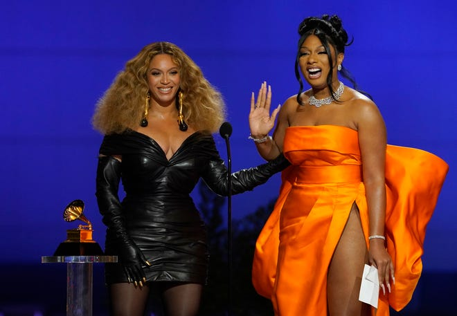 """Beyonce, left, and Megan Thee Stallion accept the award for best rap song for """"Savage"""" at the 63rd annual Grammy Awards at the Los Angeles Convention Center on Sunday, March 14, 2021. (AP Photo/Chris Pizzello)"""