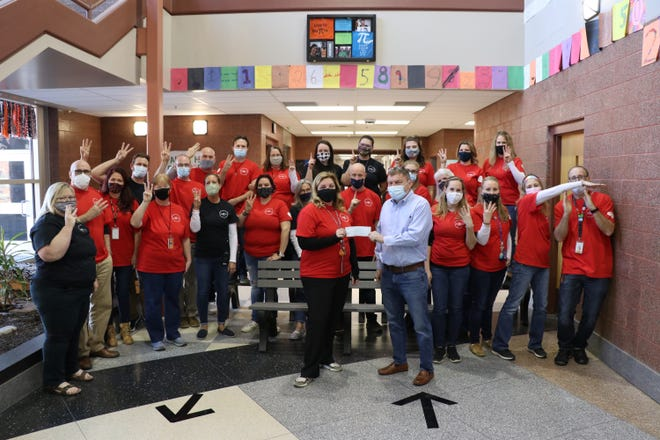 """Sturgis Public Schools personnel pose under a memorial plaque for Ellen Eisele with their """"Pi Day"""" shirts and gesture """"3.14,"""" as a check is presented to a memorial fund for classroom grants and student scholarships."""