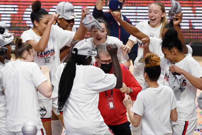 UConn head coach Geno Auriemma, center, dances with his team in celebration of their NCAA college basketball game win in the Big East tournament finals against Marquette at Mohegan Sun Arena on March 8, 2021, in Uncasville.