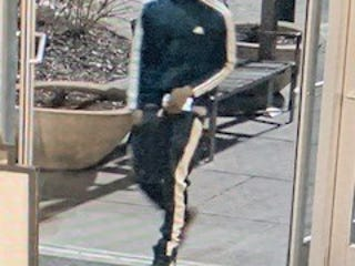 Suspect one, shown here, is described as having a black 2-inch twist hairstyle with a tapered cut. He was wearing a blue Adidas jogging suit with white stripes down the sides of the arms and legs, and black, red and white Nike Air Max shoes.