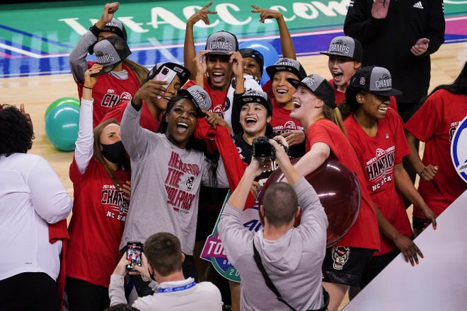 NC State teammates and coach Wes Moore celebrate their ACC Tournament championship victory over Louisville at Greensboro Coliseum on March 7.