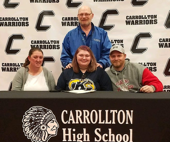 Signing a Letter of Intent to attend Kent State University Tuscarawas is Carenda Fowler seated between her mother Ashley and stepfather Matthew Fowler, while Delbert Fowler, her father, looks on from behind.
