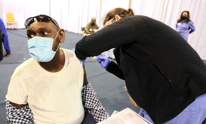 Donald Tidwell receives a shot from UAMS nurse Barbara McDonald at a clinic at Shorter College in North Little Rock.