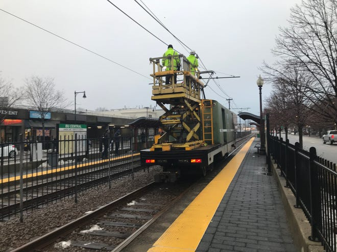 Two workers travel along the Green Line in an MBTA Power Department Wire Car in Boston.