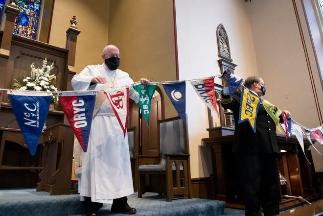 Deacon Frank Bateman, left, and Capt. Raymond Oset, right, hold aloft a string of pennants during the presentation of flags at the annual Blessing of the Fleet at Mariner's Church of Detroit on Sunday, March 14, 2021.