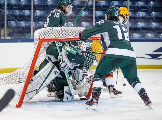 Michigan State's Tommy Miller (12) tries to keep the net off of Pierce Charleson (29) during the Michigan State vs. Minnesota Big Ten Hockey Tournament game Sunday, March 14, 2021 at the Compton Family Ice Arena in South Bend.