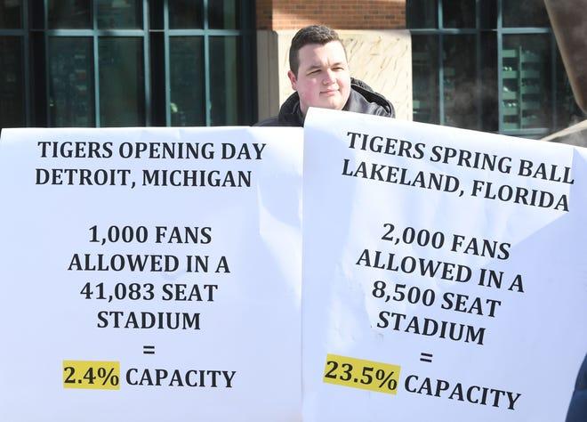 Trey Clements, putra negara bagian Rep. TC Clements dari Distrik ke-56, memegang tanda-tanda yang mendukung lebih banyak penggemar pada Hari Pembukaan untuk musim Macan.