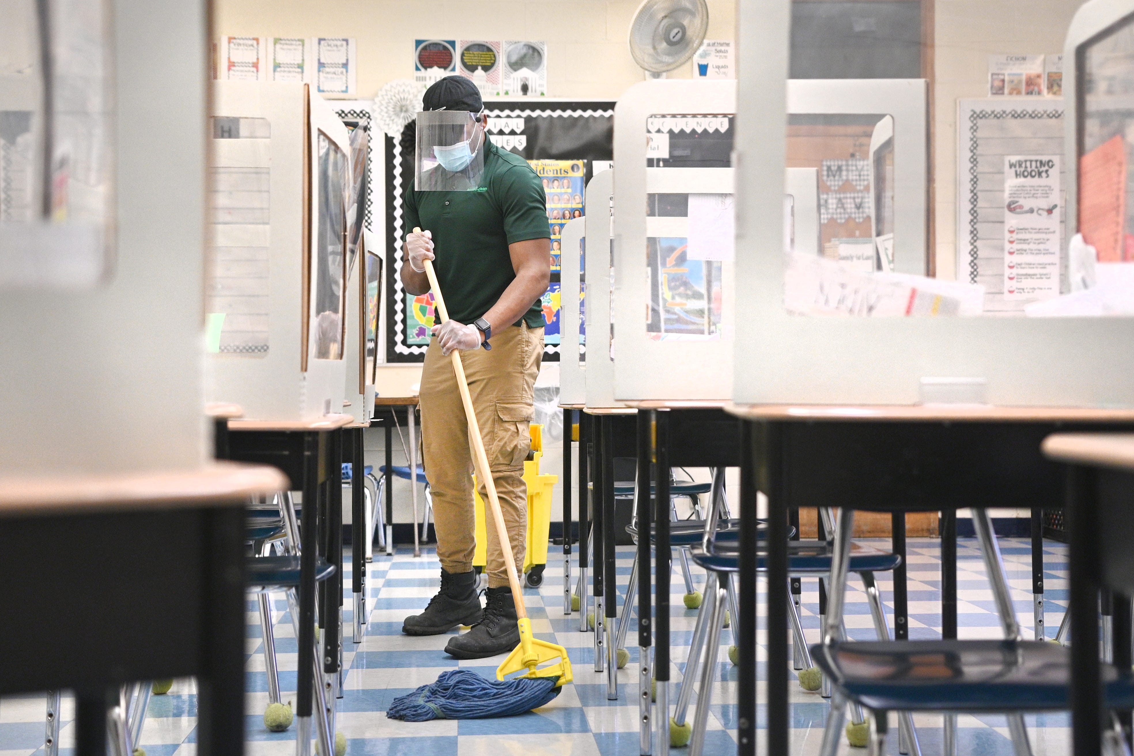 Johnathan Land mops a classroom floor at Bedford Elementary School in Dearborn Heights