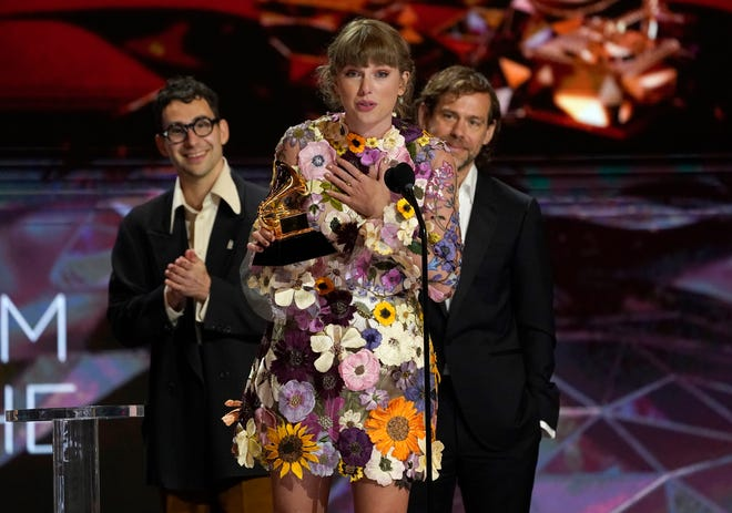 "Taylor Swift menerima penghargaan untuk album terbaik tahun ini ""Cerita rakyat""pada Penghargaan Grammy tahunan ke-63 di Los Angeles Convention Center pada hari Minggu, 14 Maret 2021. Latar belakang Jack Antonoff, kiri, dan Aaron Dessner."