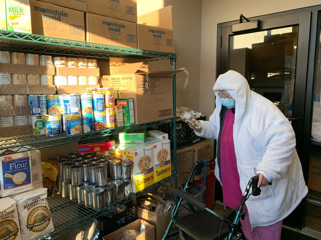 A Green Bay resident picks up food at the New Community Shelter, 301 Mather St., on March 11, 2021, in Green Bay. Food pickup runs from 5 p.m. to 6 p.m. The shelter has seen a surge in demand from community members for food and meals due to the pandemic.
