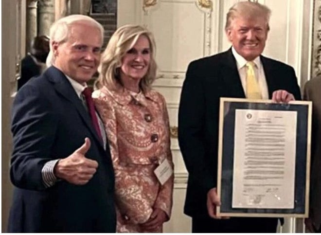Perry Hooper, a former co-chair of the Donald Trump campaign in Alabama, and U.S. Senate candidate Lynda Blanchard present former President Donald Trump with a resolution honoring his presidency at Mar-A-Lago in Palm Beach, Fla. on March 13, 2021.