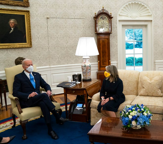 In this Friday, Feb. 12, 2021, photo, President Joe Biden. left, speaks with New Mexico Gov. Michelle Lujan Grisham during a meeting with a bipartisan group of mayors and governors to discuss a coronavirus relief package, in the Oval Office of the White House in Washington.