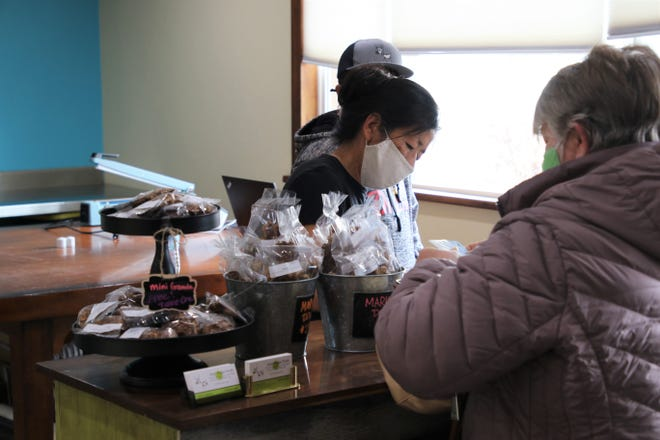 Aztec Rogue Foods co-owner Greta Quintana, center, assists a customer on Monday, March 15, 2021, in Aztec.