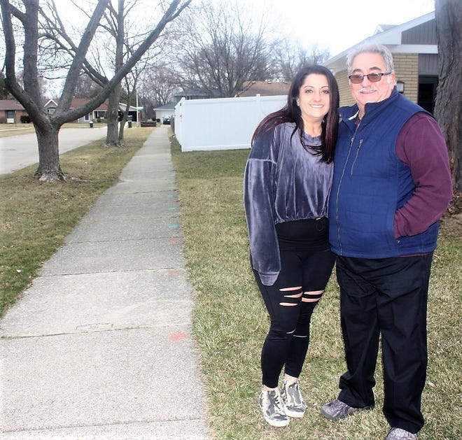 Danielle Daniels and her father Dennis Orlewicz stand next to the string of sidewalk slabs that Canton Township has marked for repair.
