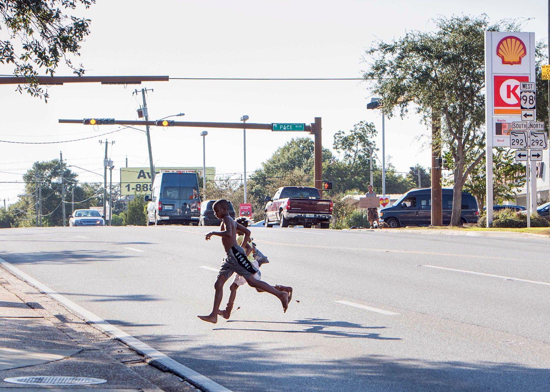Children cross Cervantes Street between breaks in vehicular traffic  near tM Street and Pace Boulevard in Sept. 2019.