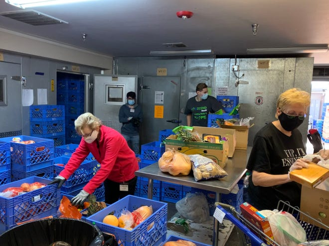 employees organizing food boxes for children and families.